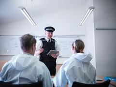 Policeman briefing forensic scientists Stock Photos