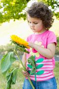 Girl examining wildflower outdoors - stock photo