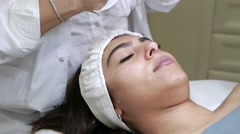 Girl starting cosmetic facial treatment  Stock Footage