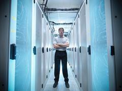 Portrait of worker standing with arms folded in computer server room Kuvituskuvat