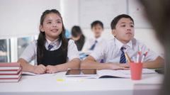 4K Happy school children in class listening to teacher & answering questions Arkistovideo