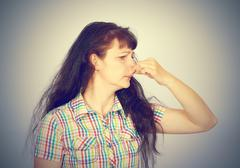 young woman holding her nose because of bad smell - stock photo