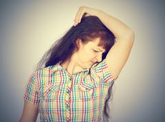 Young woman, smelling, sniffing her armpit Stock Photos