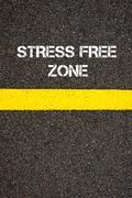 Road marking yellow line words STRESS FREE ZONE - stock photo