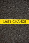 Road marking yellow line with words LAST CHANCE Stock Photos