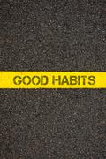 Road marking yellow line with words GOOD HABITS - stock photo