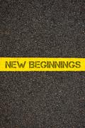 Road marking yellow line with words NEW BEGINNINGS - stock photo