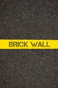 Road marking yellow line with words BRICK WALL - stock photo