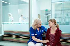 Nurse talking to woman in hospital waiting room Kuvituskuvat