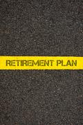 Road marking yellow line words RETIREMENT PLAN - stock photo