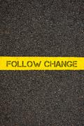Road marking yellow line with words FOLLOW CHANGE - stock photo