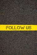 Stock Photo of Road marking yellow line with words FOLLOW US