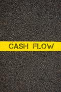 Road marking yellow line with words CASH FLOW - stock photo