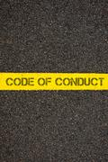 Road marking yellow line with words CODE OF CONDUCT Stock Photos
