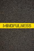 Road marking yellow line with word MINDFULNESS - stock photo