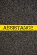 Road marking yellow line with word ASSISTANCE - stock photo