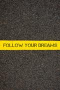 Road marking yellow line with words FOLLOW YOUR DREAMS Stock Photos