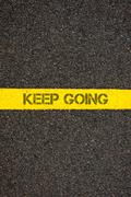Stock Photo of Road marking yellow line with words KEEP GOING