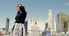 Slow motion young women with Downtown Los Angeles background 4K - stock footage