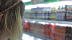 Attractive woman thinks which beverages to buy - stock footage