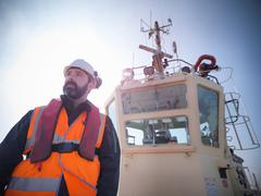 Stock Photo of Sailor wearing protective workwear on bow of tugboat