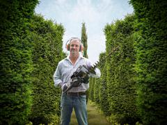 Stock Photo of Portrait of gardener wearing ear protectors and visor holding hedge trimmer
