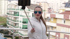 Young happy woman taking self portrait standing on the roof of the house using Stock Footage