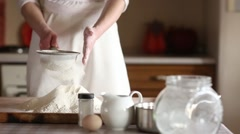 Young woman sifting flour into bowl at the kitchen Stock Footage