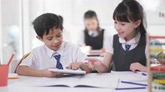 4K Happy little boy & girl looking at computer tablet in school classroom Stock Footage