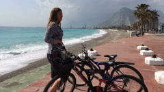 Young woman stay near bikes on seafront. Closeup Stock Footage