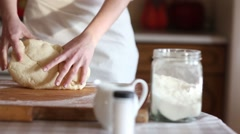 Baker hands kneading dough in flour on table, slow motion - stock footage