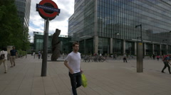 Underground sign and a modern statue in Canary Wharf business district of London Stock Footage