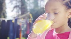 Young girl enjoying a glass of orange in the garden on a sunny day Stock Footage