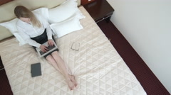 High angle view of businesswoman lying on bed in hotel room and working, laptop Stock Footage