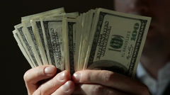 Closeup Male Hands Count Hundred Dollar Bills in the Dark Stock Footage