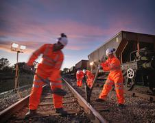 Railway workers with spade and tools working on railway tracks at night Stock Photos