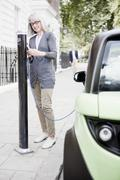 Woman charging electric car on street Stock Photos