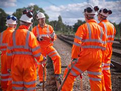 Foreman instructing railway workers on railway tracks Stock Photos