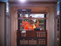 Railway worker working on railway signal electrics, view through equipment - stock photo