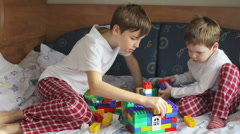 Two brothers in pajamas playing constructor on the bed Stock Footage