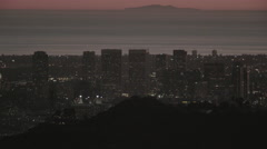 Helicopter flies over city skyline and ocean on sunset (UNGRADED) Stock Footage