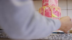 Baker applying melted coloured chocolate to a tiered cake, in slow motion Stock Footage