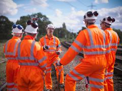 Foreman instructing railway workers on railway tracks Stock Photos