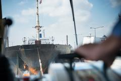 Captain adjusting engine power of tugboat towing ship Stock Photos