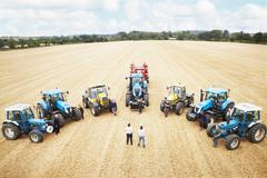 Farmers with tractors in crop field Stock Photos
