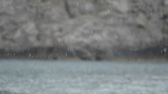 Rain On Calm Sea With Rocks In Background Stock Footage