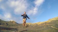 Man running down sand dune slow motion Stock Footage