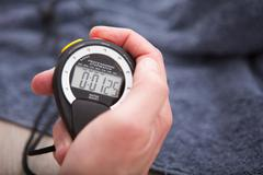 Close up of hand holding stopwatch Stock Photos