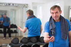 Trainer holding stopwatch in gym Stock Photos