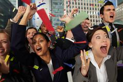 Businesspeople cheering as ticker tape falls Stock Photos